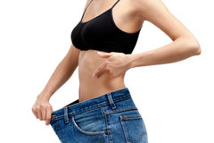 Body of a slim girl wearing big jeans Stock Photography