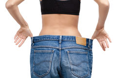 Body of a slim girl wearing enormous jeans Royalty Free Stock Photo