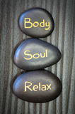 Body, soul, relax. Black lava stone with words body, soul, relax Stock Photo