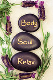 Body, soul, relax. Black lava stone with words body, soul, relax Royalty Free Stock Photo