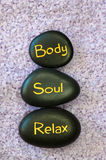 Body, soul, relax. Black lava stone with words body, soul, relax Royalty Free Stock Photos