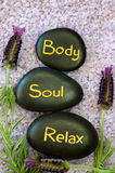 Body, soul, relax. Black lava stone with words body, soul, relax Royalty Free Stock Images