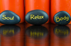 Body, soul and relax concept. Burning orange candles and black lava stones Stock Images