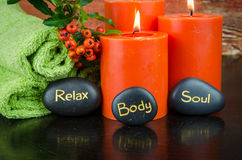 Body, soul and relax concept. Burning orange candles,orange berry, lava stone and towel still life Royalty Free Stock Image