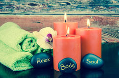 Body, soul and relax concept. Burning orange candles,orange berry, lava stone and towel still life Royalty Free Stock Images