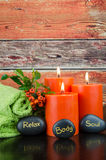 Body, soul and relax concept. Burning orange candles,orange berry, lava stones and green towel still life Royalty Free Stock Photography