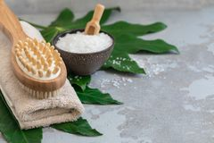 Body spa treatment bamboo brush with bath towel, salt m on green tropical leaf background stock photo