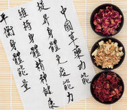 Body and Spirit Health. Chinese herbal medicine with peony, jasmine and rose petal flowers with mandarin calligraphy script on rice paper. Translation describes Stock Photos