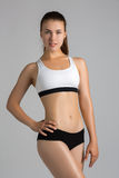 The body sports an attractive woman on a gray background. Fitness Royalty Free Stock Photography