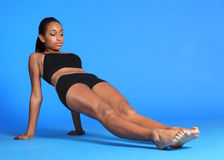 Body stretch by beautiful African American woman. Body and torso stretch exercise by beautiful young athletic african american fitness woman wearing black sports Stock Images