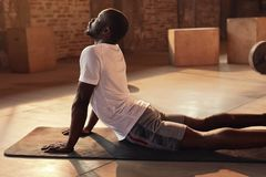 Body stretch. Fit man stretching back, doing yoga workout at gym