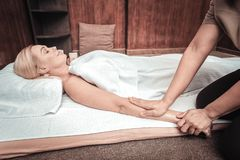 Nice skilled masseuse holding her clients hand. Body therapy. Nice skilled masseuse holding her clients hand while performing body massage stock images