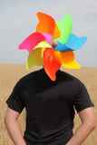 Body with toy wind turbine at field. Surrealism photo Stock Photo