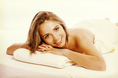 Body treatment concept.. Beautiful young woman lying on front and looking at camera Royalty Free Stock Photography