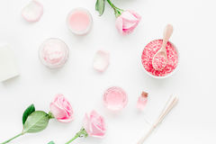 Body treatment with rose flowers and cosmetic set white desk background top view Royalty Free Stock Image