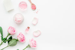Body treatment with rose flowers and cosmetic set white desk background top view space for text. Body treatment with rose flowers and cosmetic set on white desk Royalty Free Stock Images