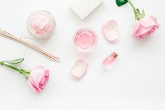Body treatment with rose flowers and cosmetic set white desk background top view space for text Stock Photography