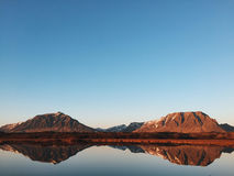 Body of Water Beside Brown Mountain during Day Time Stock Images