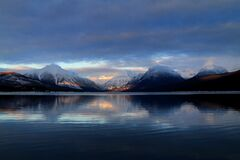 Body of Water in a Distant of Mountains Under White Clouds Stock Image