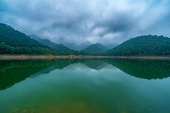 Body of Water Near Green Tree Mountain Under Cloudy Sky Stock Image