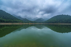 Body of Water Near Green Tree Mountain Under Cloudy Sky Royalty Free Stock Photography