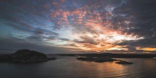 Body of Water Near Mountains Taken Under Orange Clouds during Sunset Royalty Free Stock Image