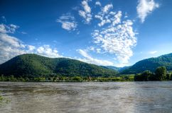 Body of Water Near Mountains Under Blue Sky royalty free stock photography