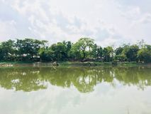 Body of Water Near Trees Under Cloudy Sky Stock Images