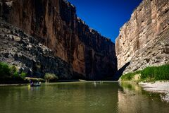 Body of Water Between Rocky Mountain Under Clear Blue Sky during Daytime Royalty Free Stock Photo