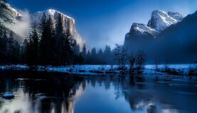 Body of Water Beside Trees by Snowfield Near Mountains Royalty Free Stock Photos