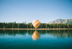 Body of Water Beside Yellow and Blue Hot Air Balloon Near Green Trees during Day Time Royalty Free Stock Image