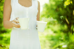 Body of woman carrying tea. Body of young woman in white dress carrying two cups of tea or coffee outdoors; green nature background Royalty Free Stock Images