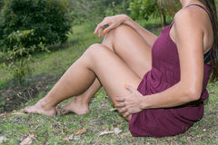 Body woman sitting on the grass with dress color purple  showing beautiful legs Stock Photo