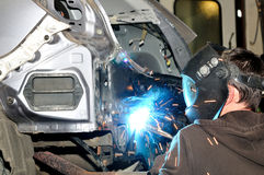 Body worker welding panels. Royalty Free Stock Images
