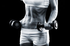 Body of a young fit woman lifting dumbbells stock photos