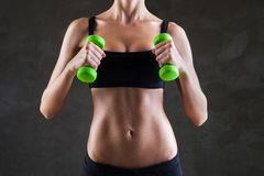 Body of young fit woman lifting dumbbells Stock Image
