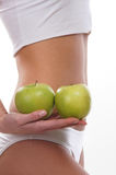 Body of a young woman holding fresh apples Royalty Free Stock Photos