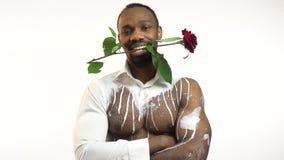 bodyart的黑人与在他的牙的一朵玫瑰由于他来有一件礼物的在他的手上,生日一名白人 股票视频