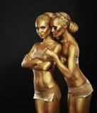 Bodyart. Flickvänner med guld- makeup i omfamning. Art Deco royaltyfri foto