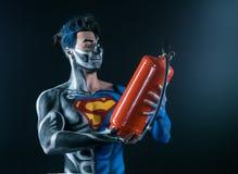 Bodyart van een super held die een brandblusapparaat in de handen houdt Stock Fotografie