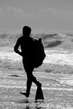 Bodyboard surfer running. Silhouette of a bodyboard surfer running on the shoreline of a beach Royalty Free Stock Images