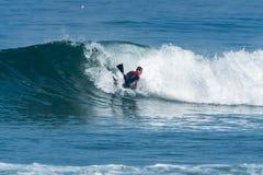 Bodyboarder som surfar havvågen Arkivbild