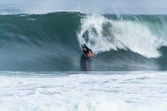 Bodyboarder som surfar havvågen Arkivbilder