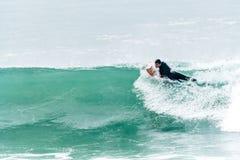 Bodyboarder som surfar havvågen Arkivfoto
