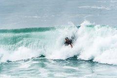 Bodyboarder som surfar havvågen Arkivfoton