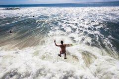 Bodyboarders que practica surf Pier Jump Ocean Foto de archivo