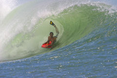 Bodyboarding the Tube of a Wave in Hawaii. A bodyboarding riding a tubing wave in Hawaii Royalty Free Stock Photography