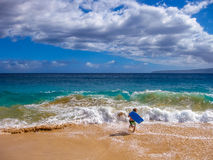 Bodyboarding Hawaii. Young boy runs on sand making bodyboarding, Big Beach, Maui in Hawaii, America Stock Photography