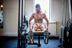 Bodybuilder établissant et s'exerçant au gymnase, aux jambes et aux pieds Photo stock