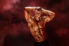 bodybuilder θέτοντας Η ικανότητα διάστισε το muscled άτομο στο κόκκινο υπόβαθρο καπνού Στοκ Εικόνες